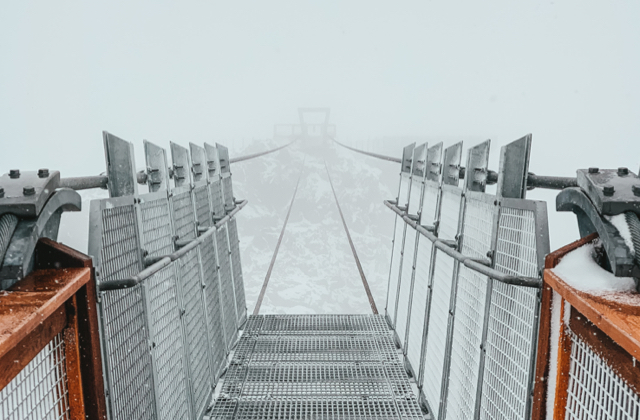 A bridge across a chasm disappearing into fog