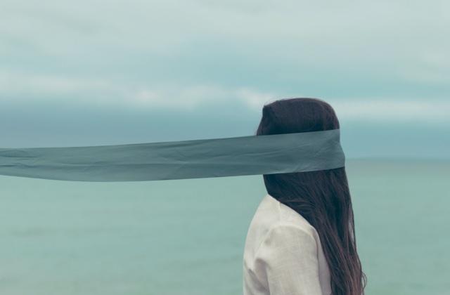 Wonam on a beach wearing a blindfold